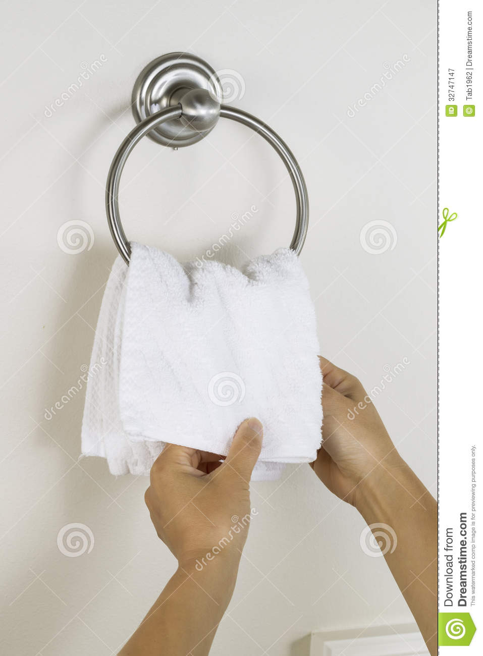 Female Hands Putting Clean Wash Cloth On Towel Ring Holder