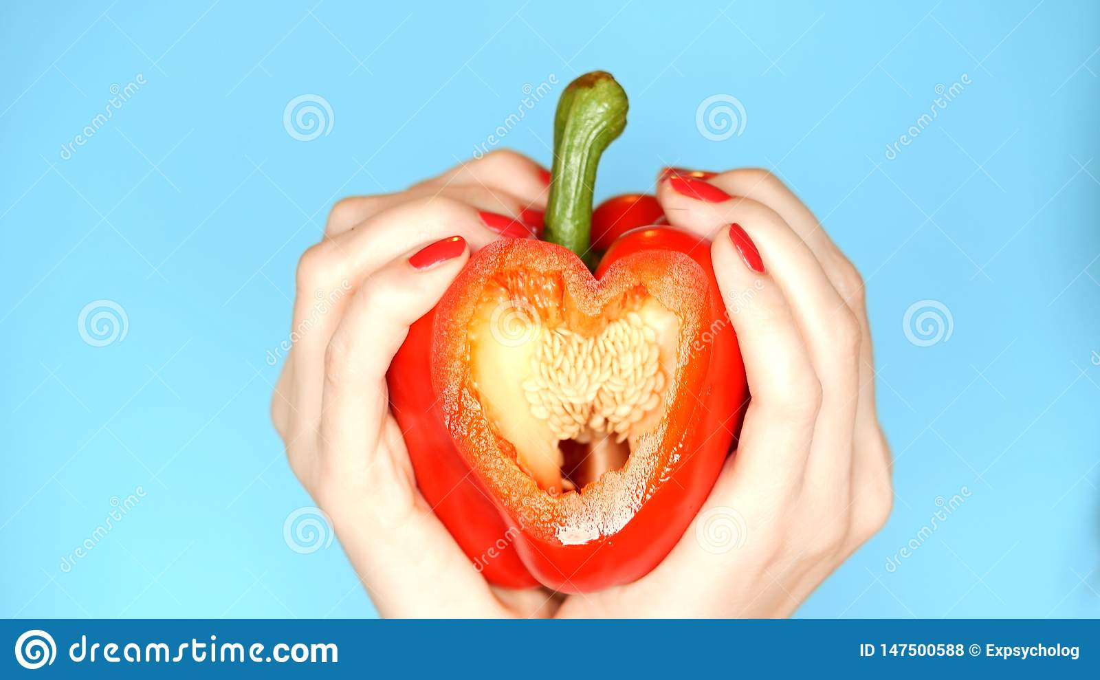 Female hands with red manicure hold red sweet pepper in hand in the form of a heart on a blue background