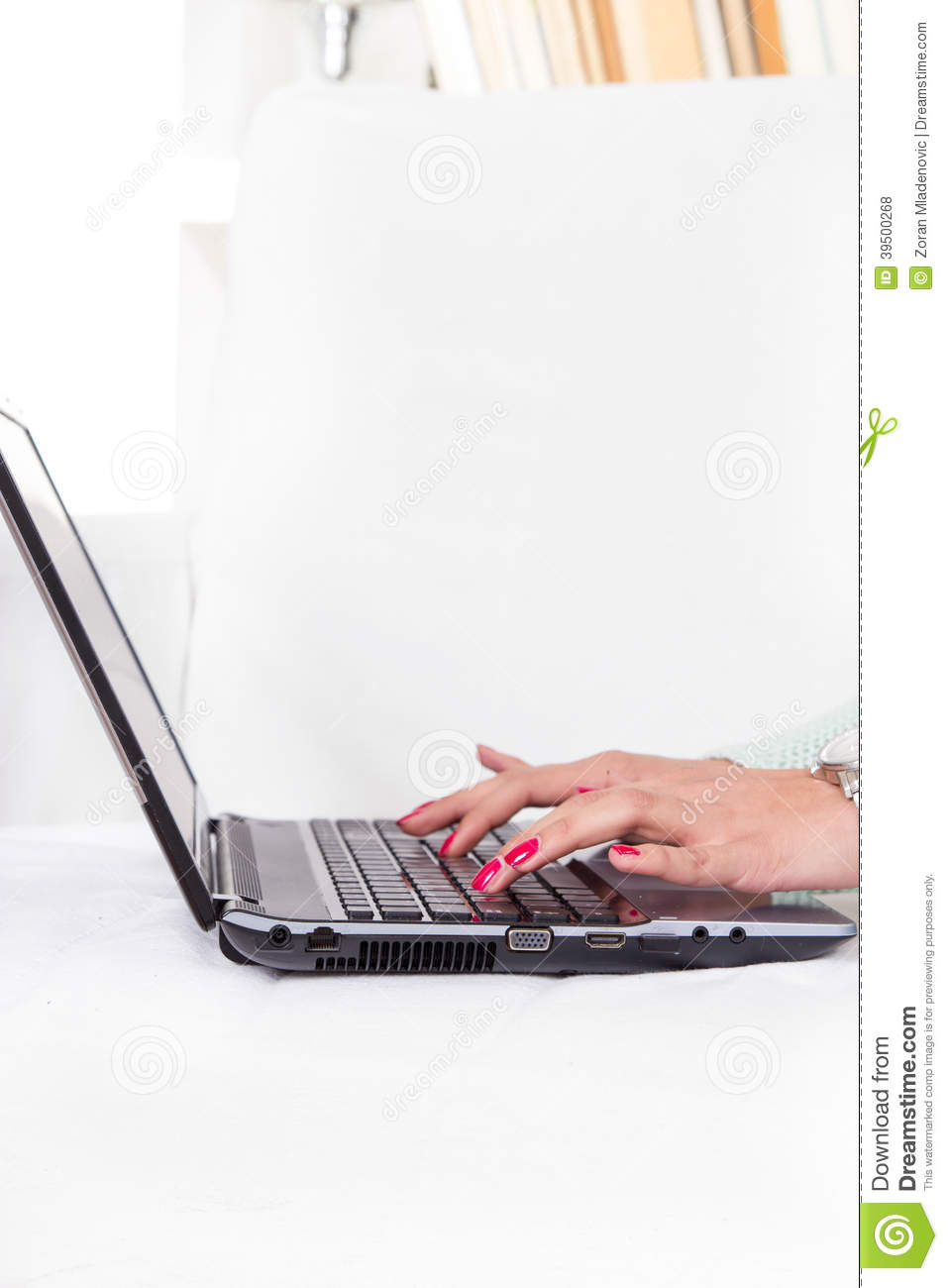 Female hands typing on laptop keyboard with red manicure