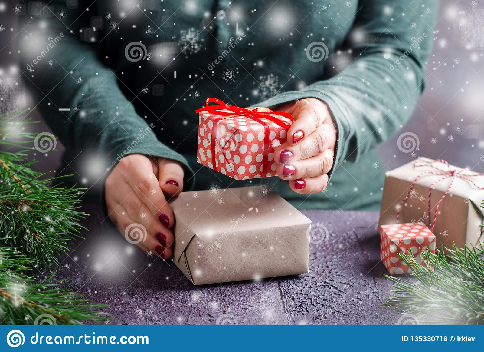 Female Hands Wrapping And Present Christmas Gifts On Dark Background
