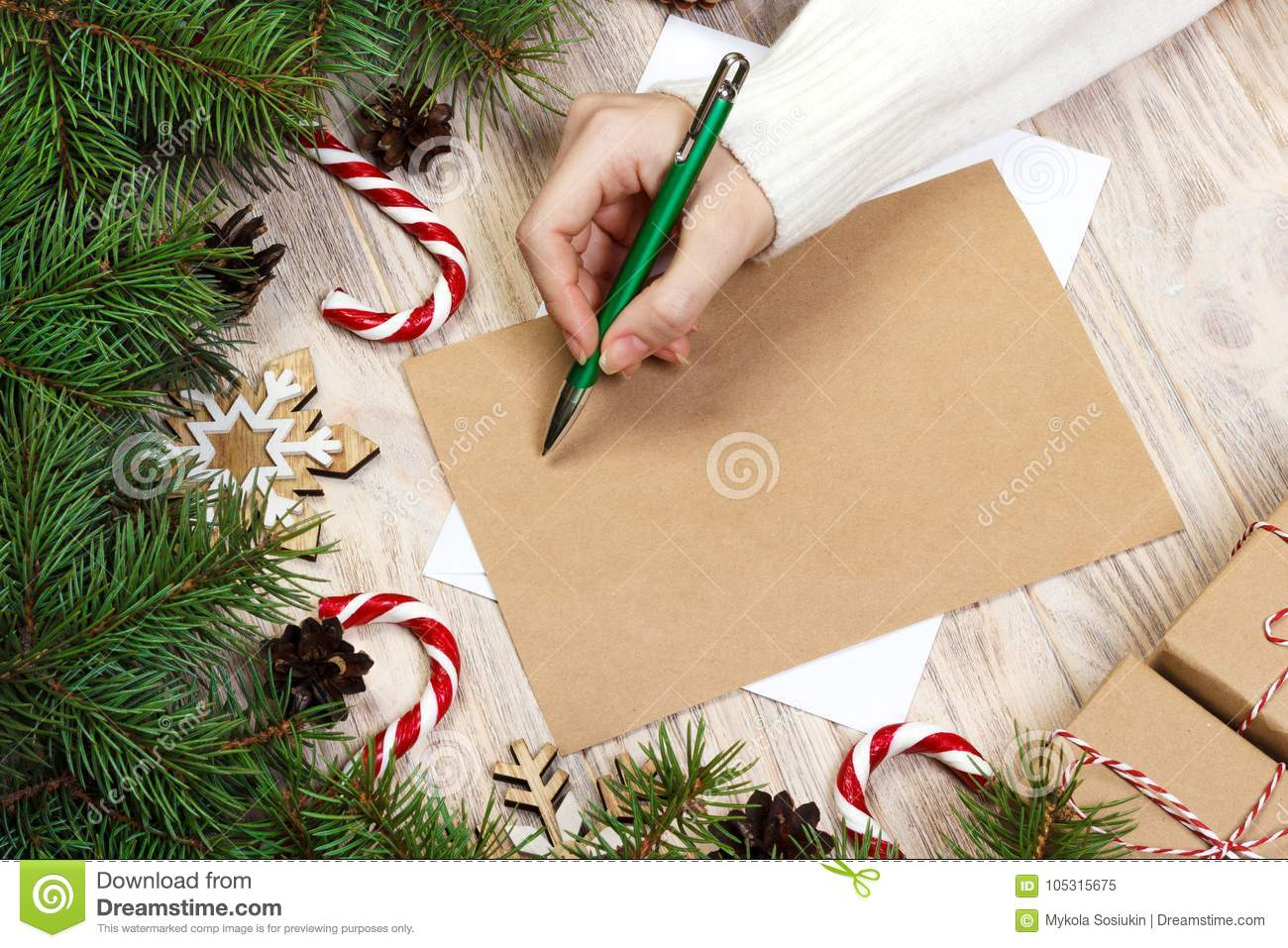Female hands writing a letter to santa claus. christmas gifts on a