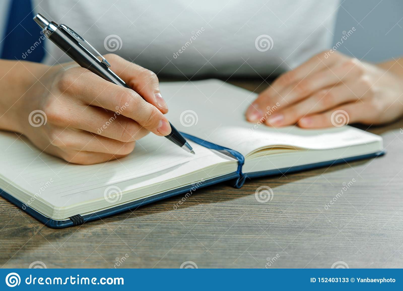 Female hands are writing in a notebook