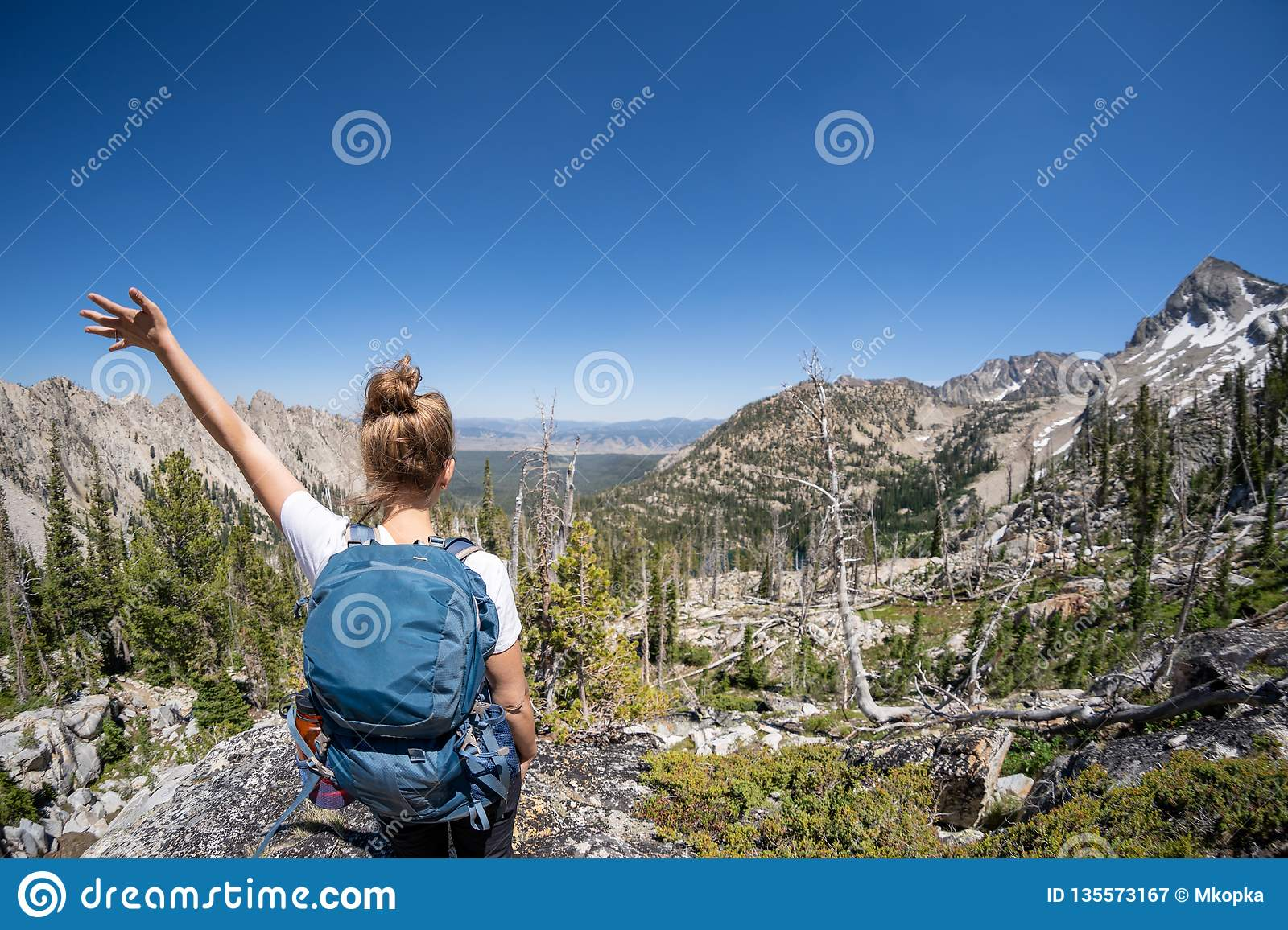 Female hiker with backpack along the Sawtooth Lake trail in Idaho. Back facing camera. Concept for solo female travel and hiking