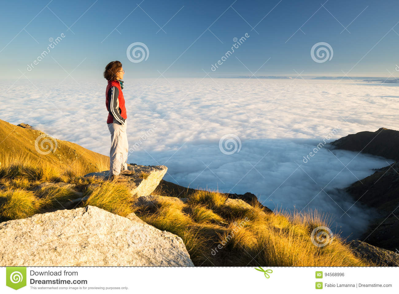 Female hiker reaching her goal at the mountain top and looking at majestic panoramic view of the italian western Alps with clouds