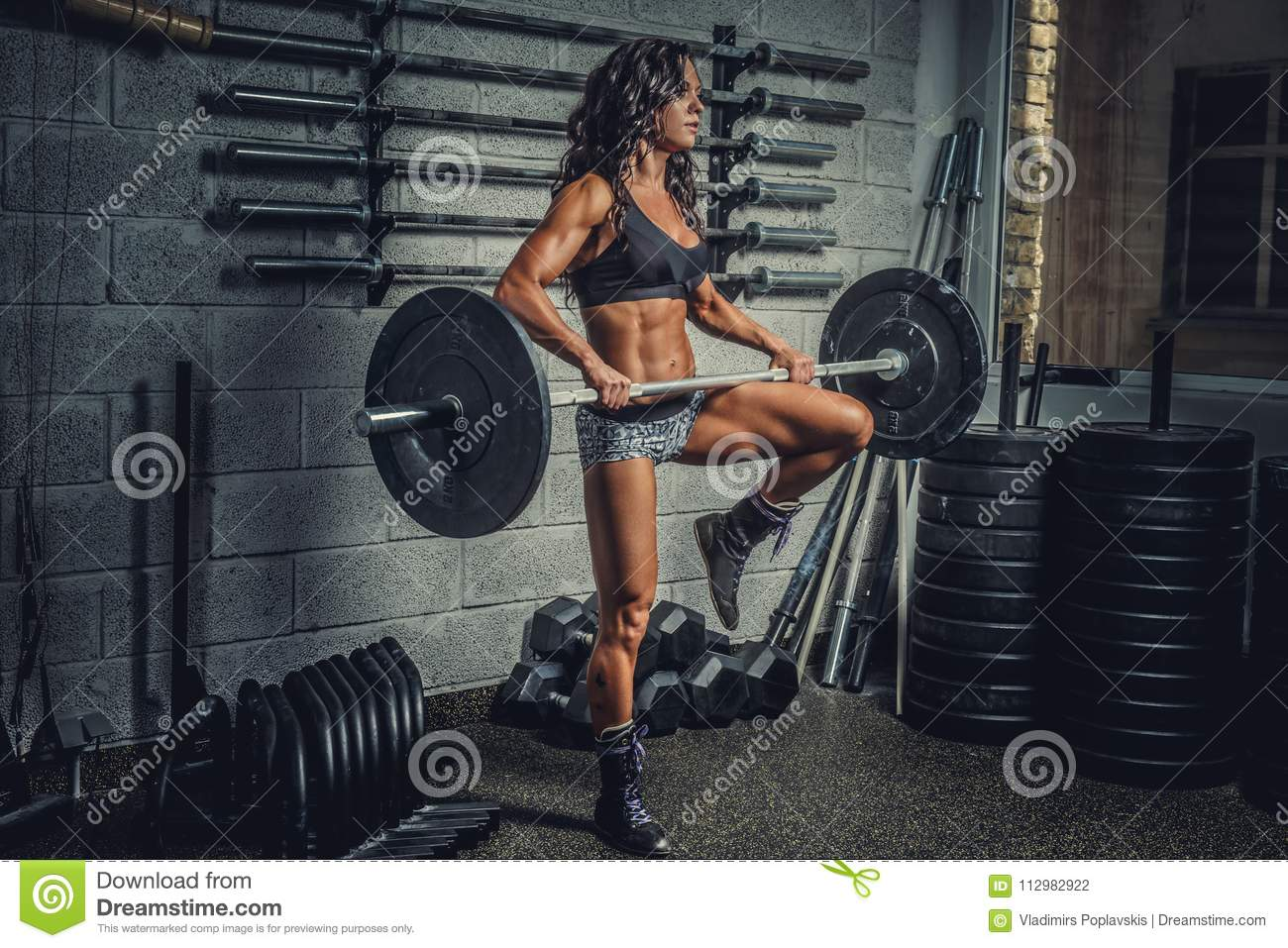 Female holding barbell in a gym club.