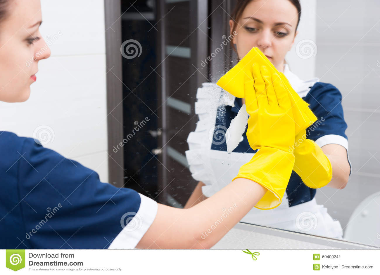 How to clean bathroom mirror - Female Hotel Maid Wiping Bathroom Mirror Stock Image