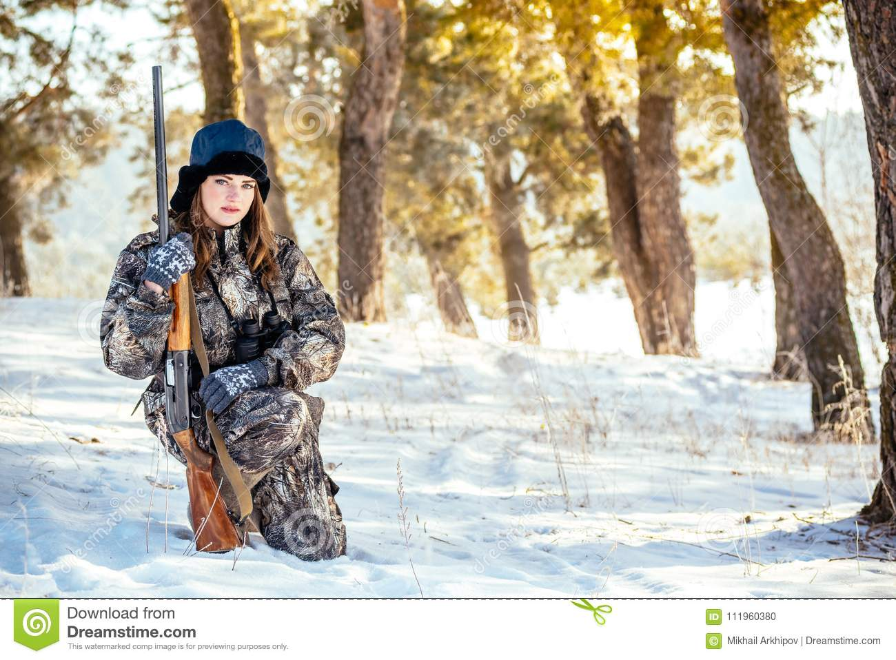 Female hunter in camouflage clothes ready to hunt, holding gun a