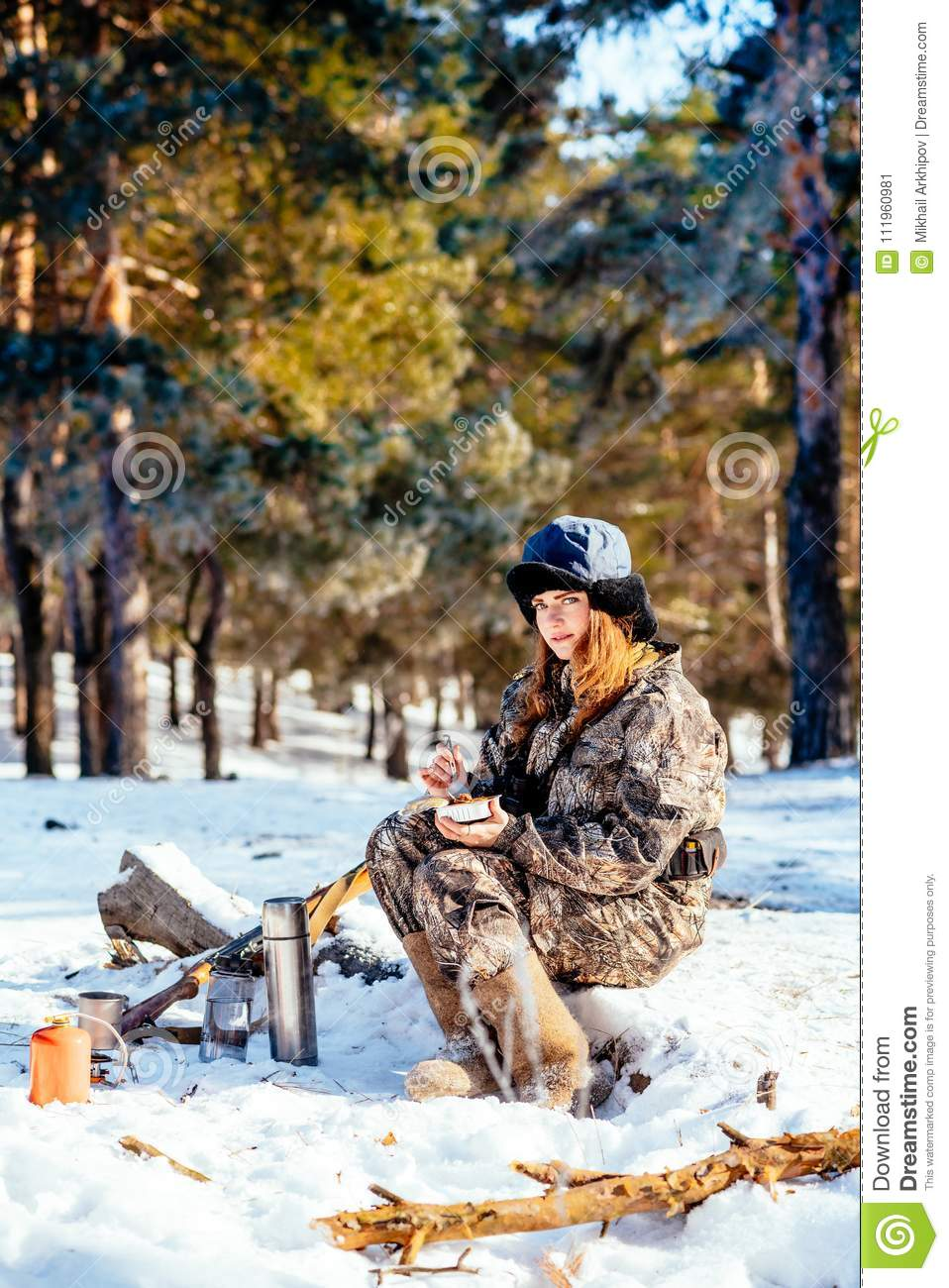 Female hunter preparing food with a portable gas burner in a win