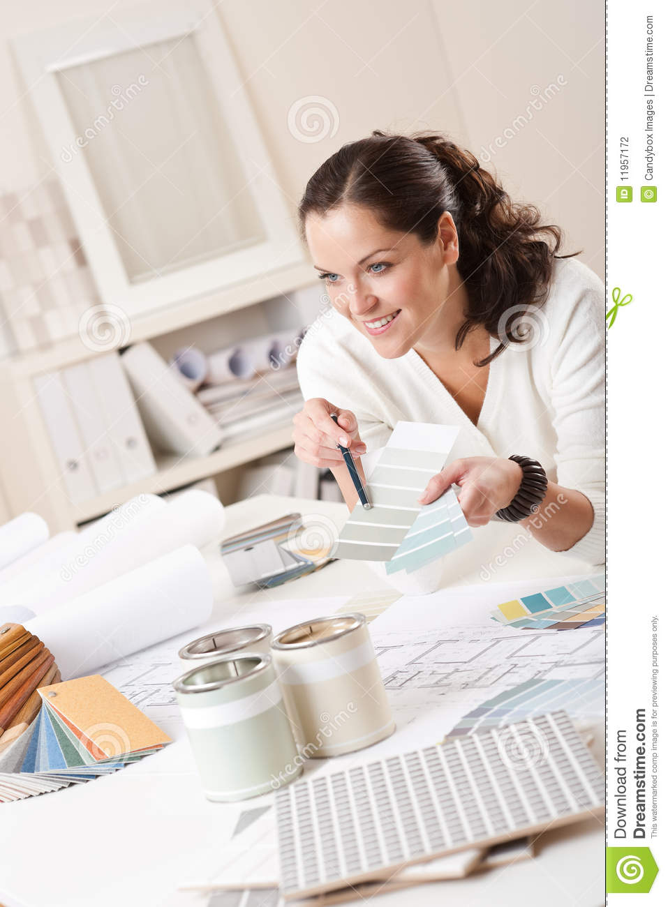 female interior designer working at office with color swatch and paint