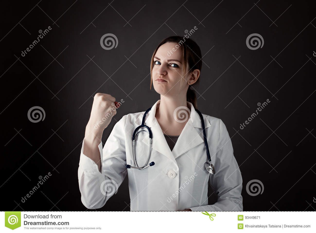 Female Intern Holds a fist and look in camera with strong face. Stethoscope or phonendoscope on neck. Medicine photo