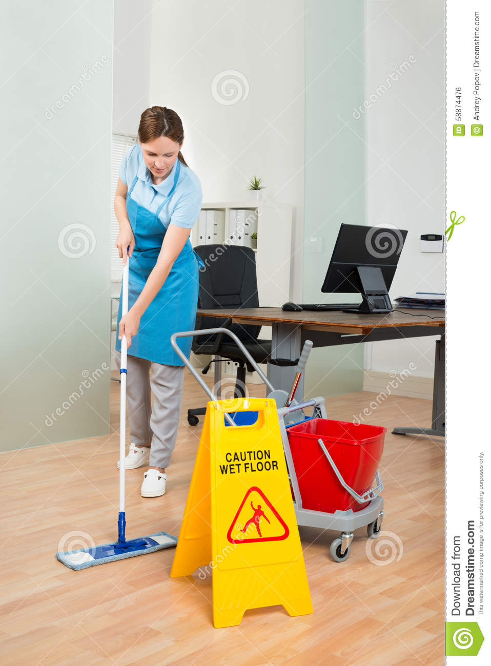 Female Janitor Cleaning Hardwood Floor In Office Stock