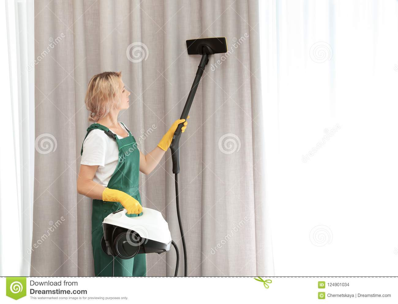 Female janitor removing dust from curtain wit
