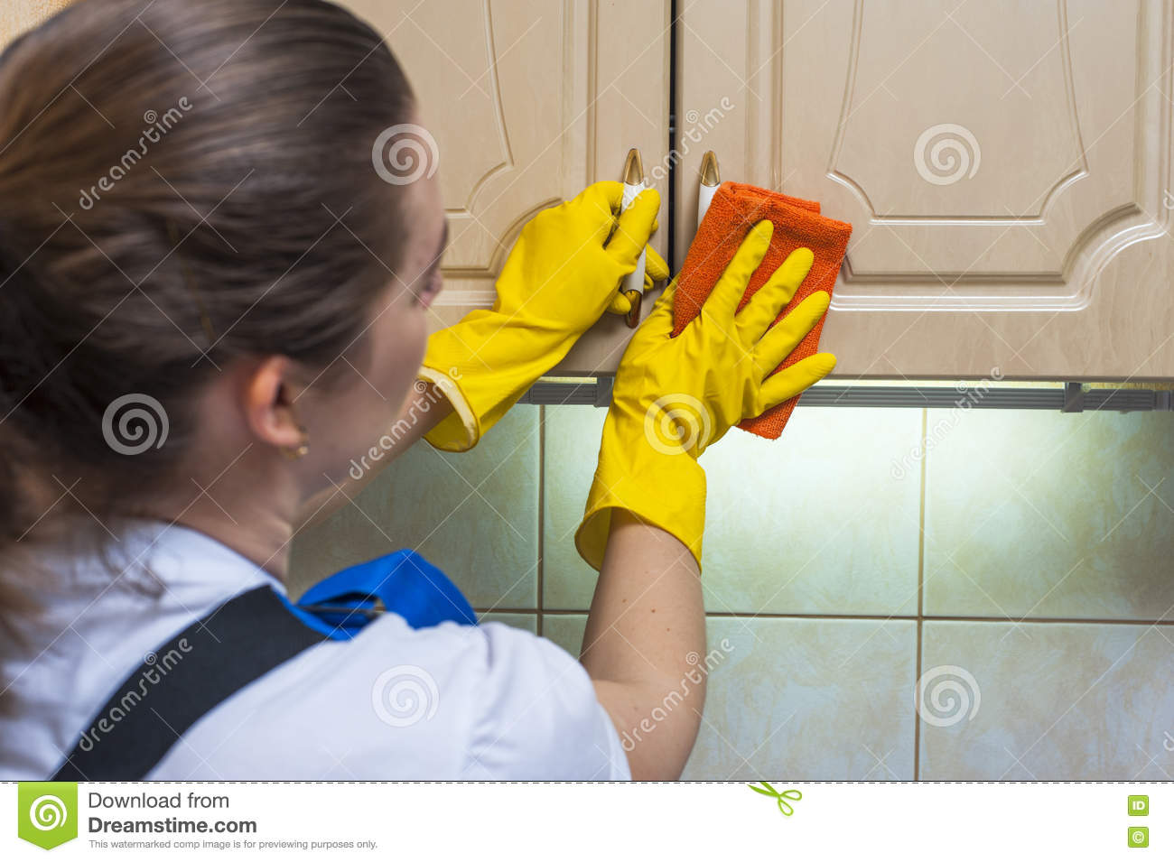 Nettoyer Les Placards De Cuisine female janitor scrubbing the kitchen cupboard with a rag