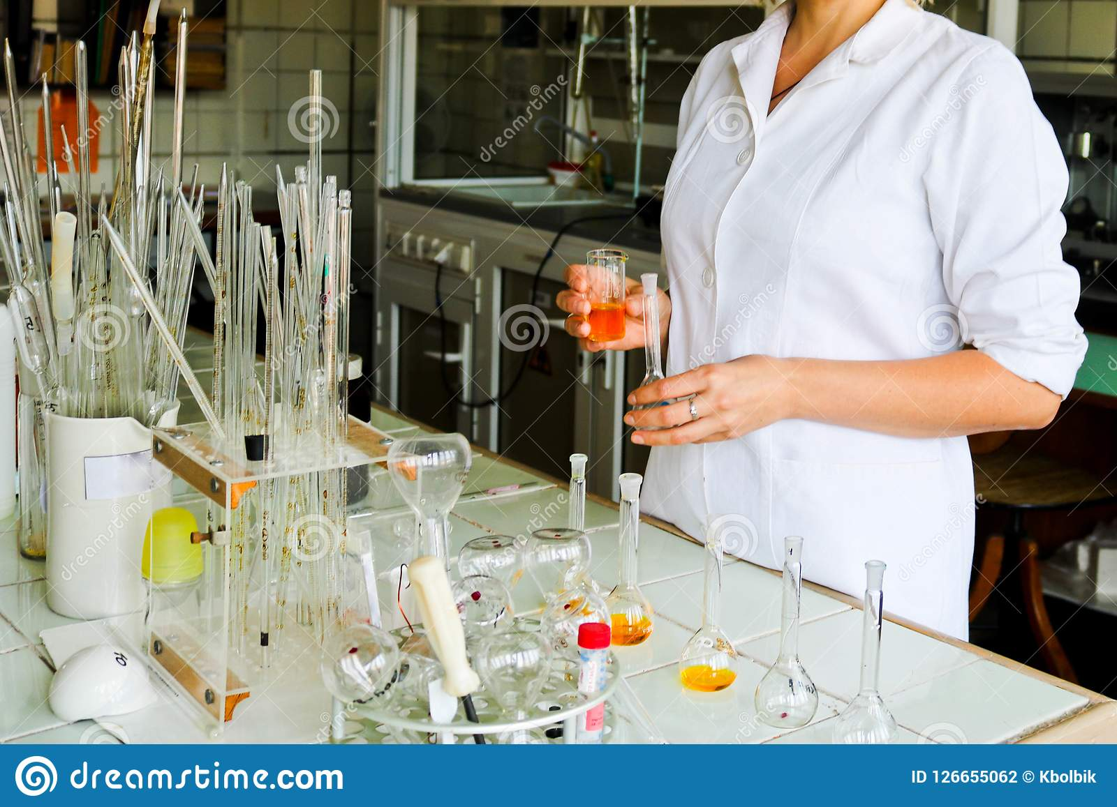 A female laboratory assistant, a doctor, a chemist, works with flasks, test tubes, makes solutions, medicines, mixes ingredients