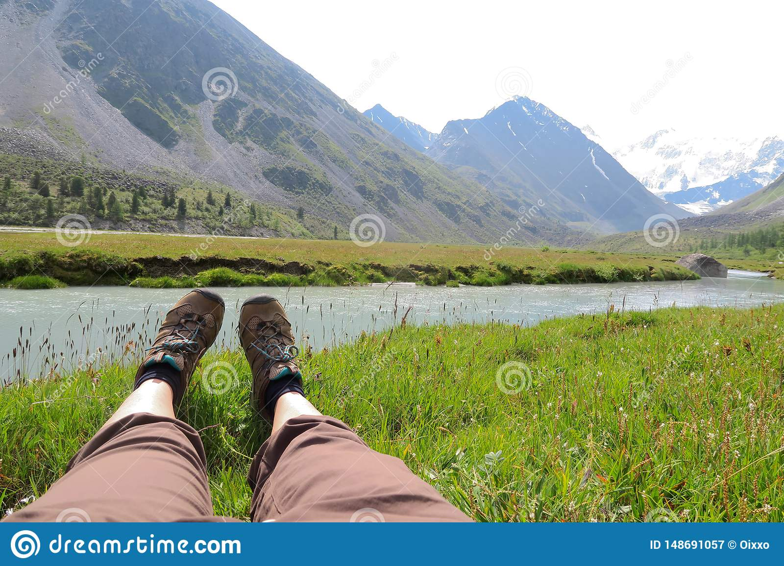 Female legs on the grass and mountains landscape on background