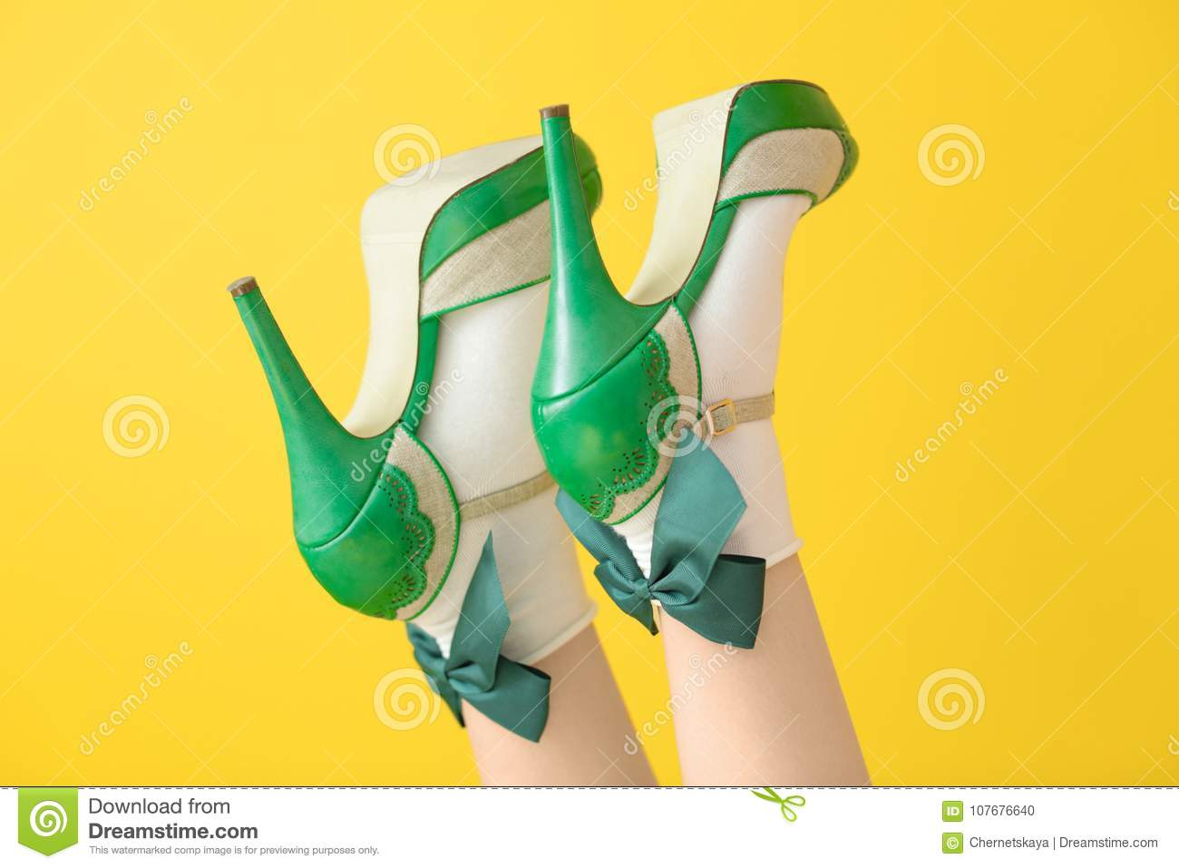 Female legs in green high heel shoes and socks