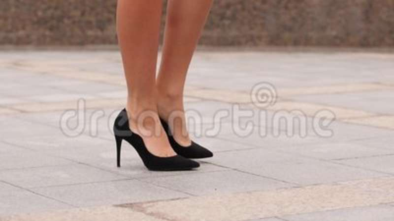 88e199087f6 Female legs in high heels shoes walking in the urban street. Feet of young  business woman in high-heeled footwear going. Motion