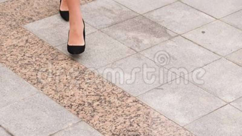 9c335a1afa9 Female legs in high heels shoes walking in the urban street. Feet of young  business woman in high-heeled footwear going. Background