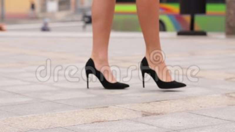 4836a979608 Female legs in high heels shoes walking in the urban street. Feet of young  business woman in high-heeled footwear going. Beautiful