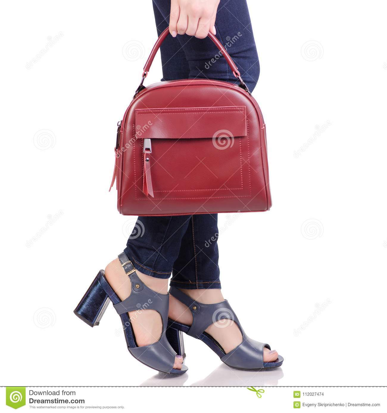 ed9ff1981 Female legs in jeans and in blue sandals shoes with red leather bag handbag  fashion beauty shop buy on white background isolation