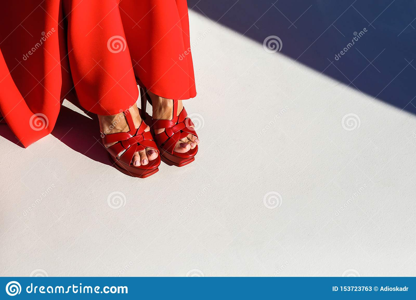 Female legs in red shoes on white background