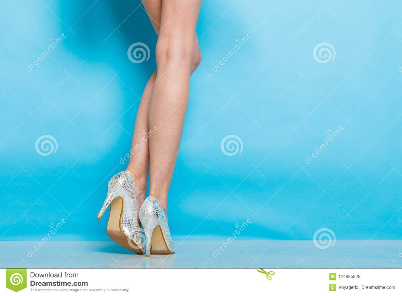 f0e03a32c1 Female fashion. Silver high heels spiked fashionable shoes on long legs.  Studio shot against blue. More similar stock images