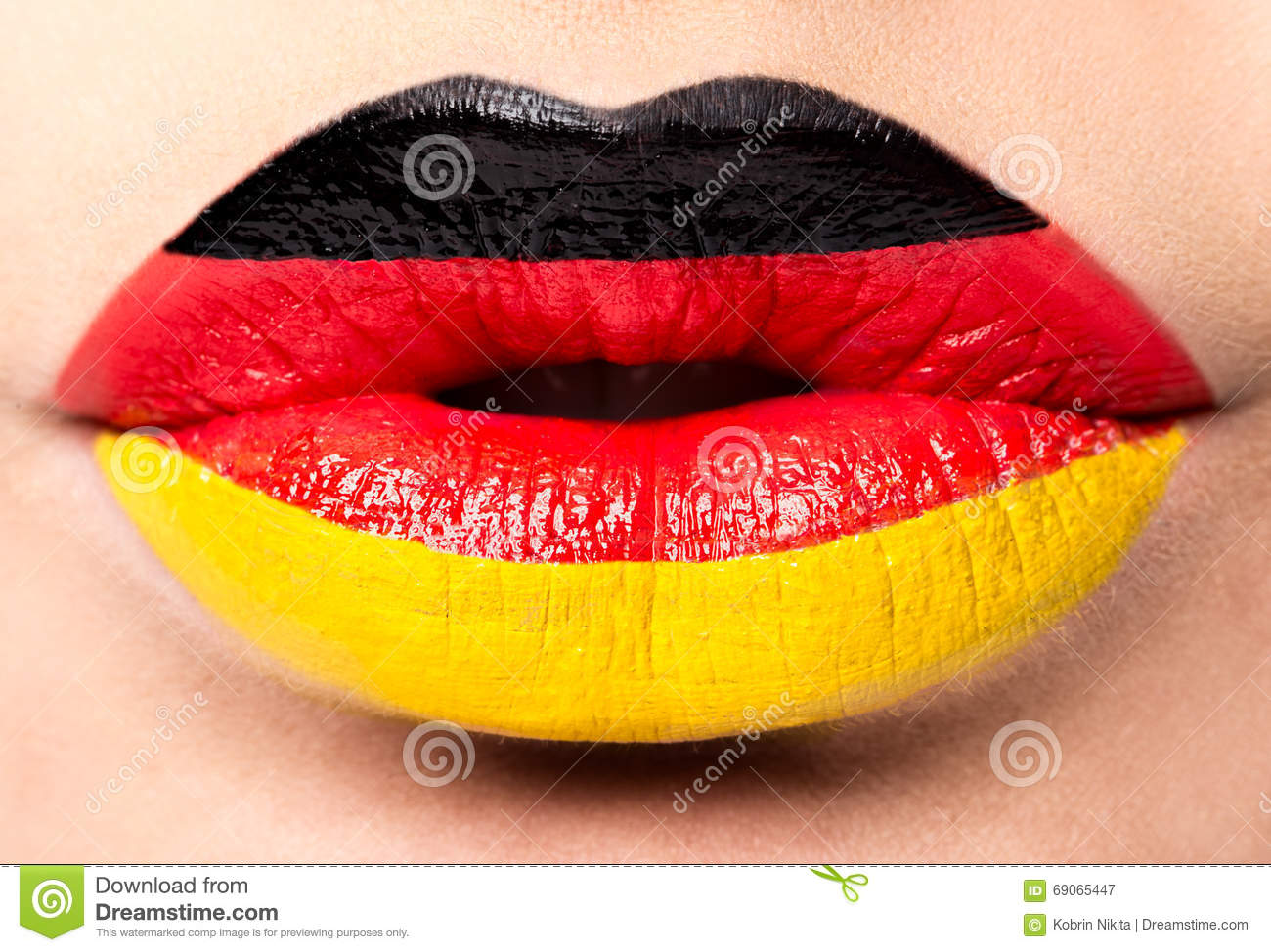 Female lips close up with a picture flag of Germany. black, red, yellow.