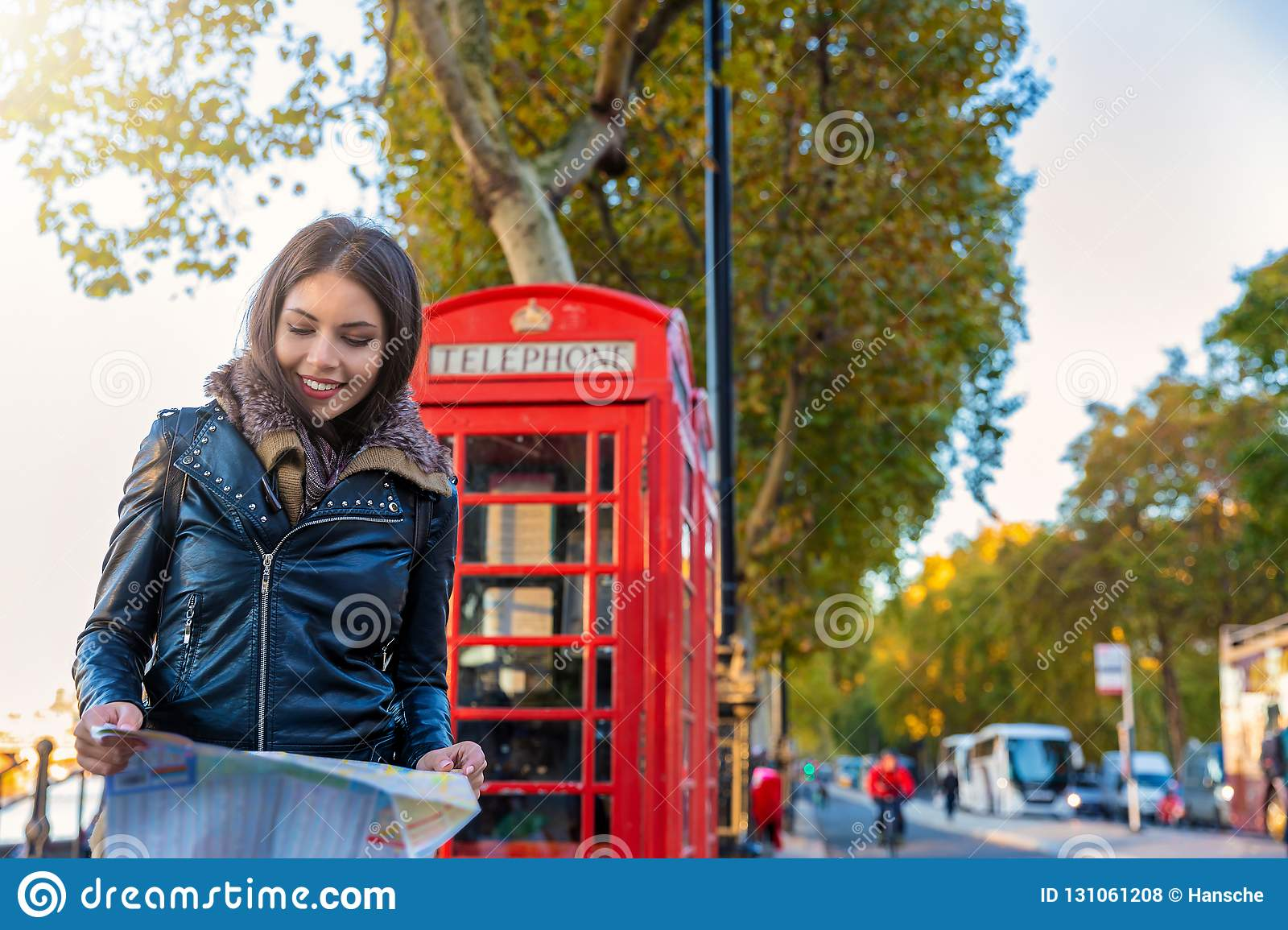 Female London tourist looks at a map in front of a red telephone booth