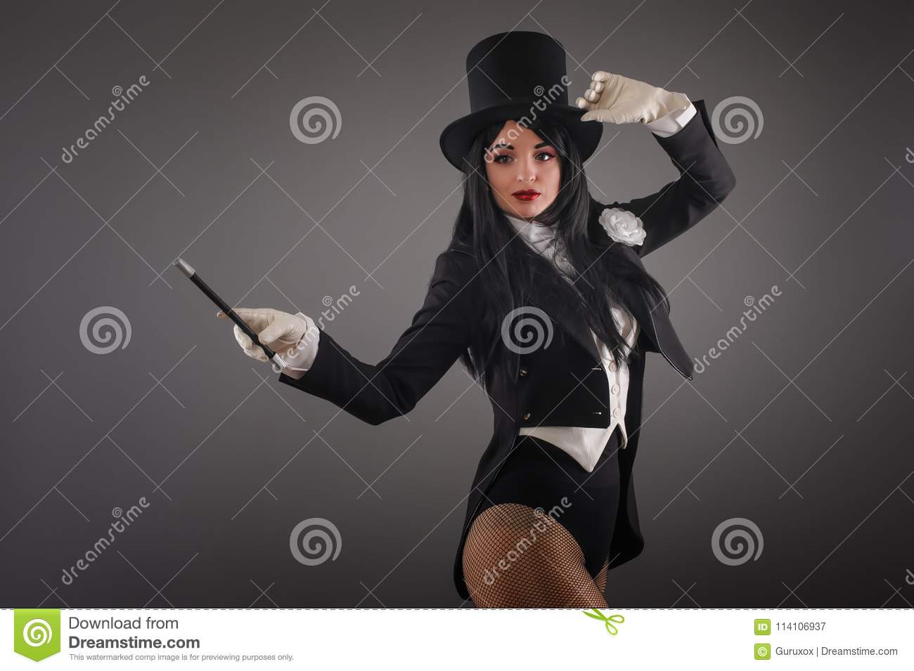 Female magician in costume suit with magic stick doing trick