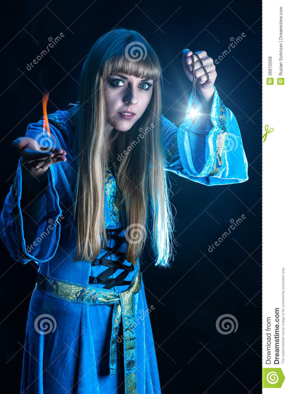 Young female magician with blond hair in blue robe holding amulet ...