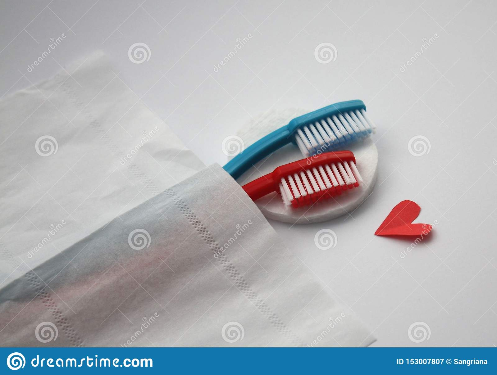 Female and male toothbrushes hugging in bed, visual metaphore of love