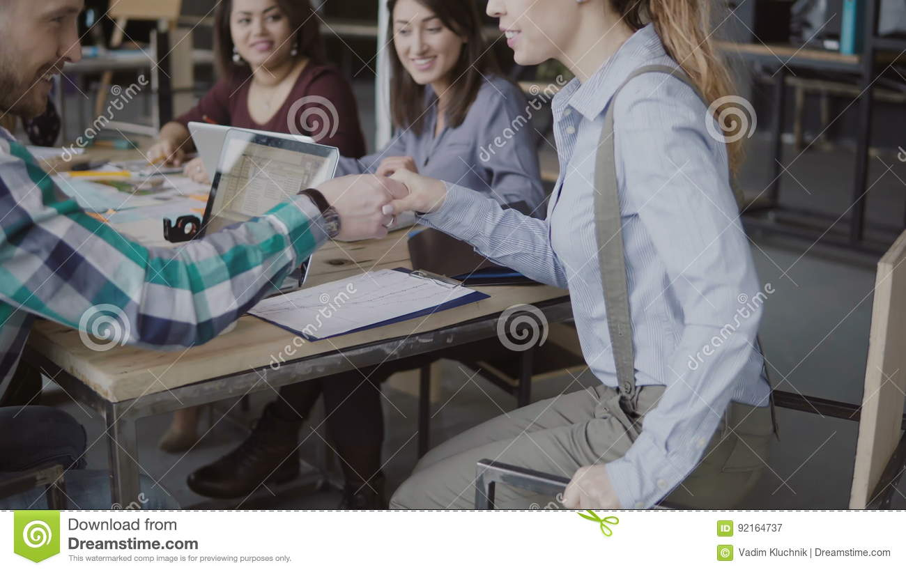 Female manager comes to team, sits at table and shakes hand to male colleague. Creative business team at modern office.