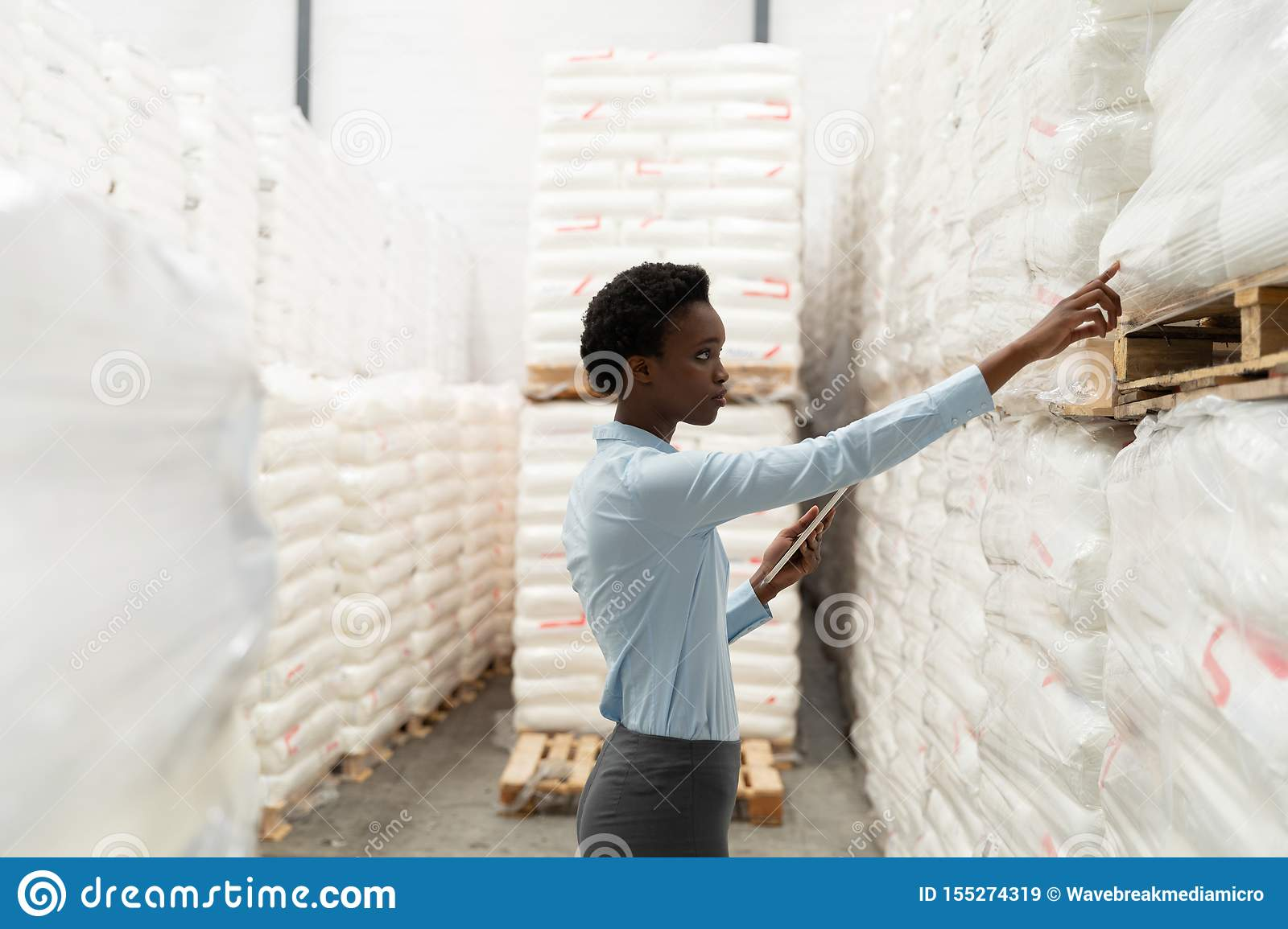 Female manager with digital tablet checking stocks in warehouse
