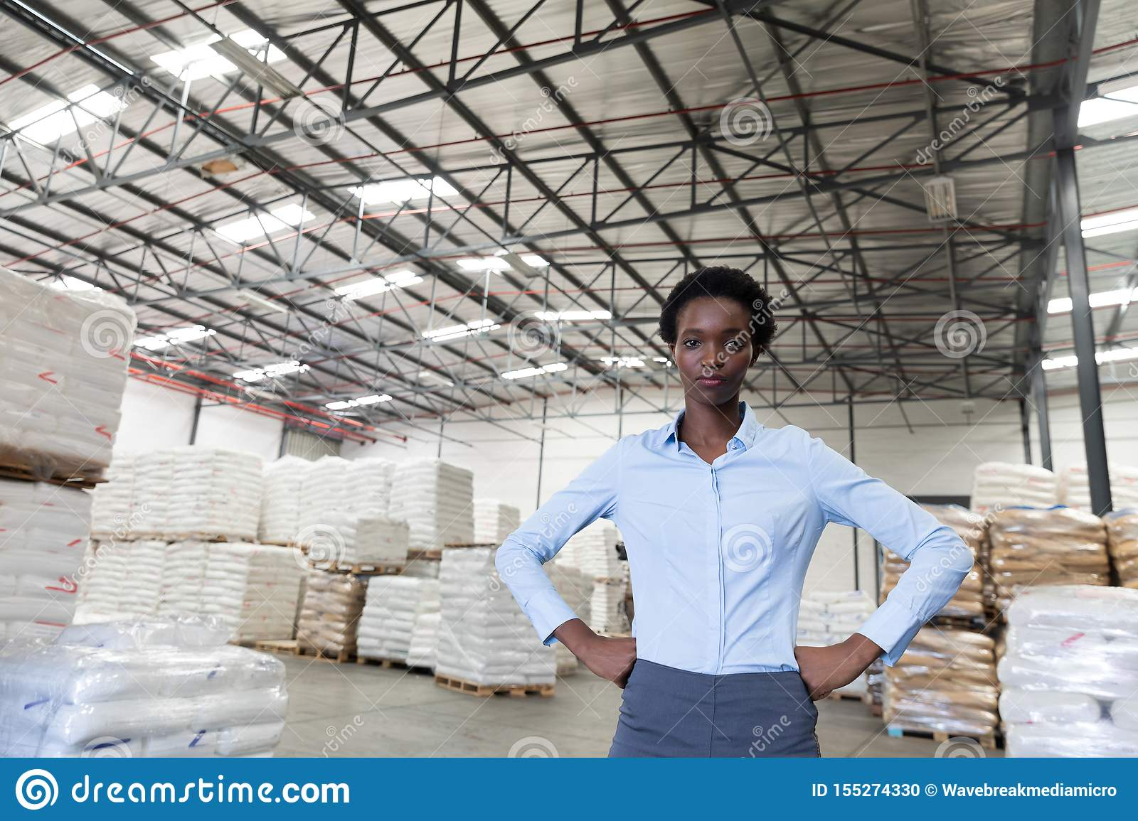 Female manager with hands on hip looking at camera in warehouse
