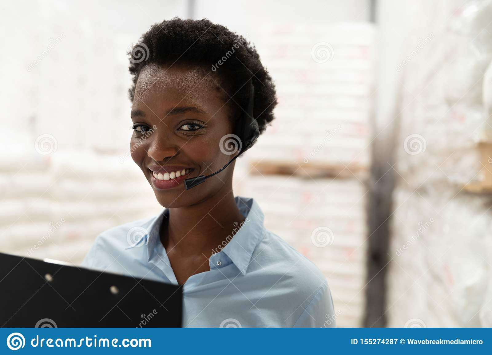 Female manager with headset and clipboard looking at camera in warehouse