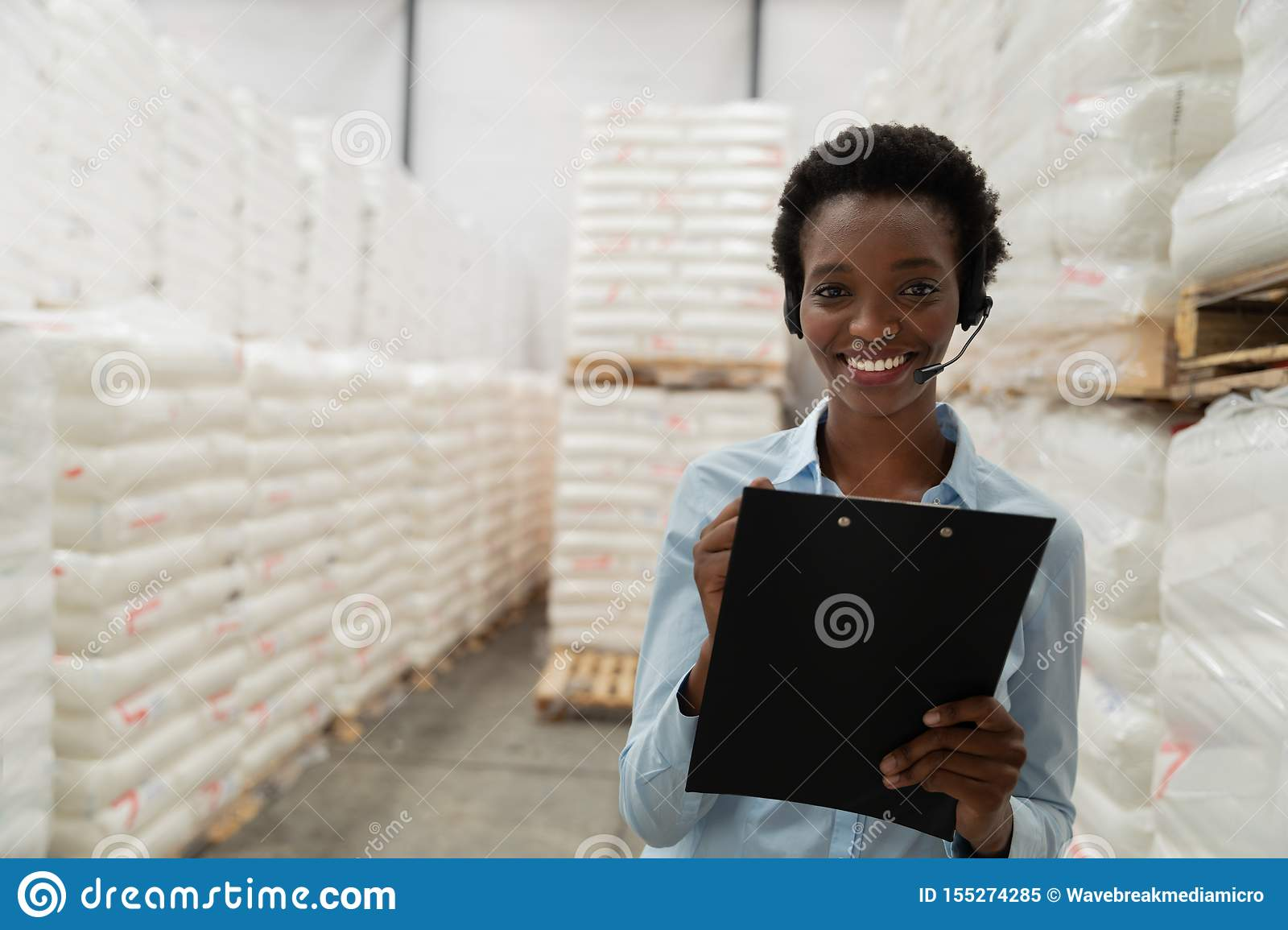 Female manager with headset writing on clipboard in warehouse