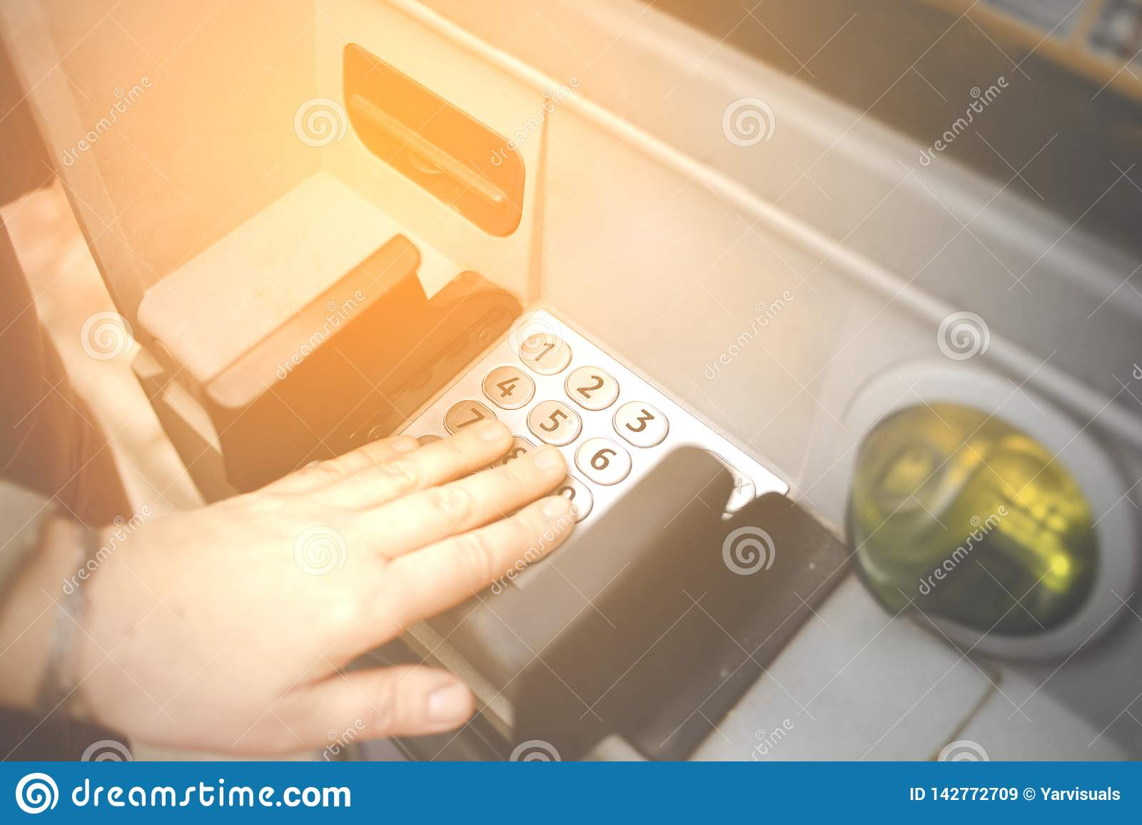 Female mature entering PIN numbers on ATM bank machine . Concept of insecure strangers , thugs , thieves online payments , robbe