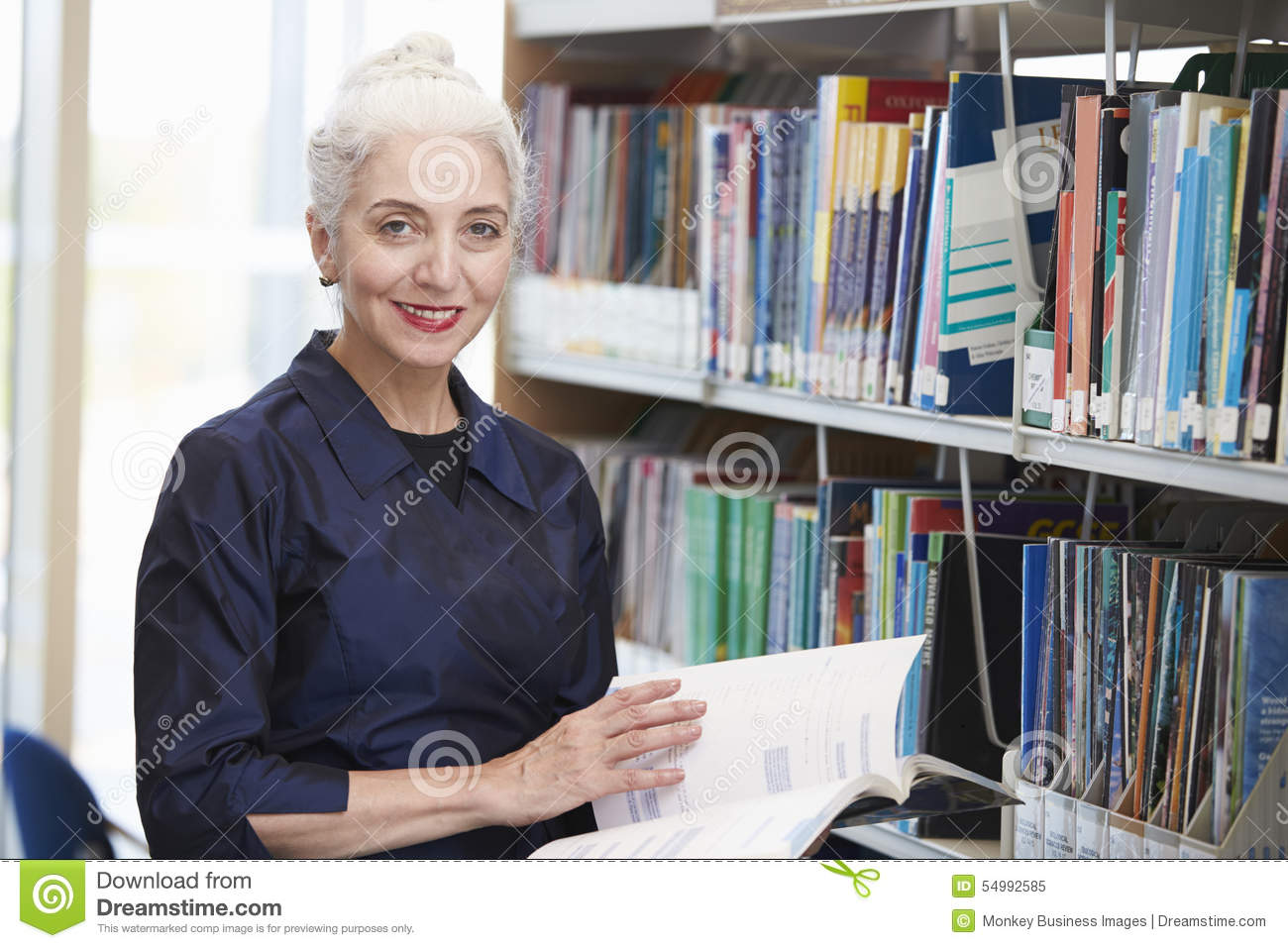 Female Mature Student Studying In Library