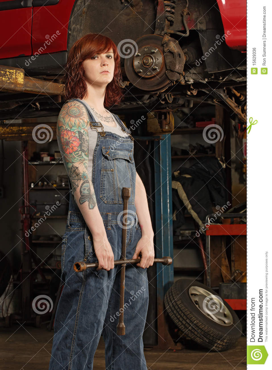 female mechanic with tire iron stock photo