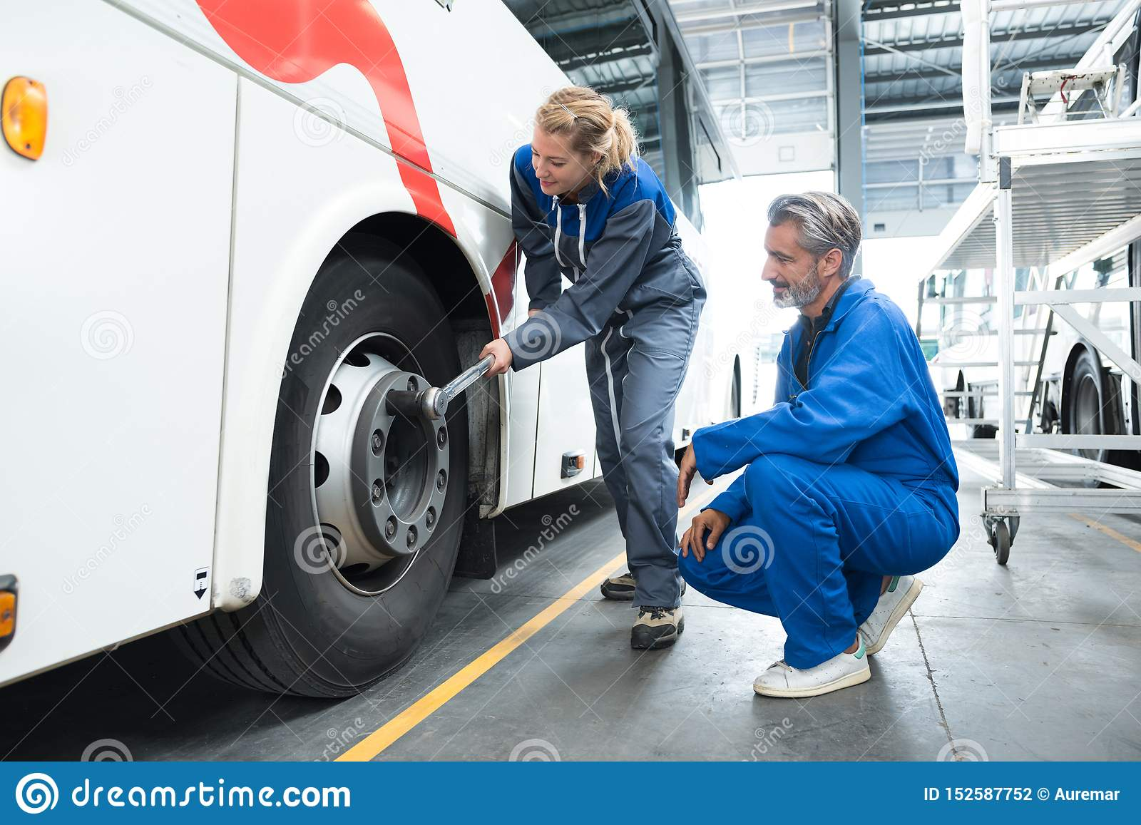 Female mechanic using tonque wrench on bus wheel nuts