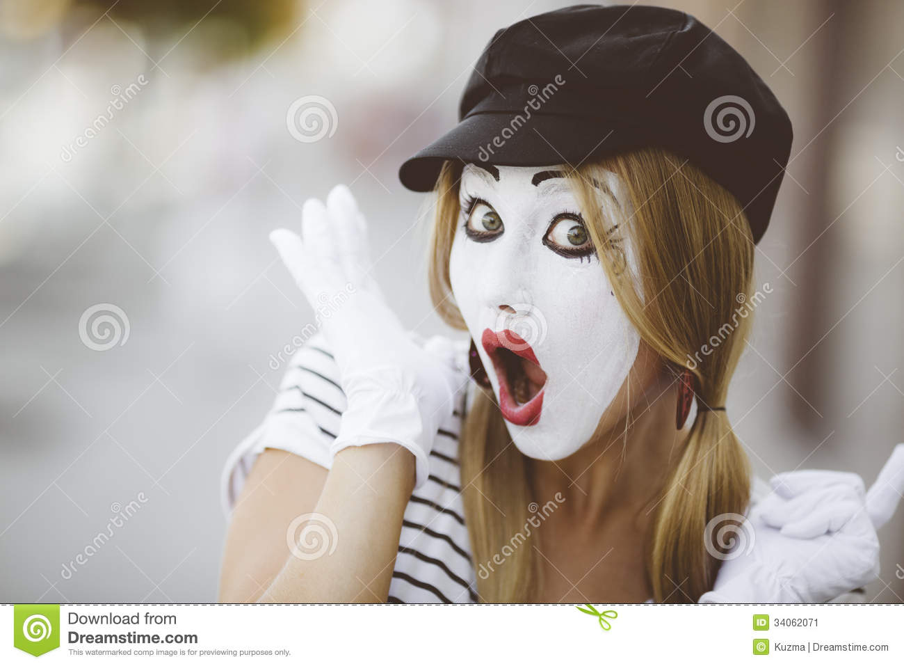 Portrait of mime with black hat and white gloves.