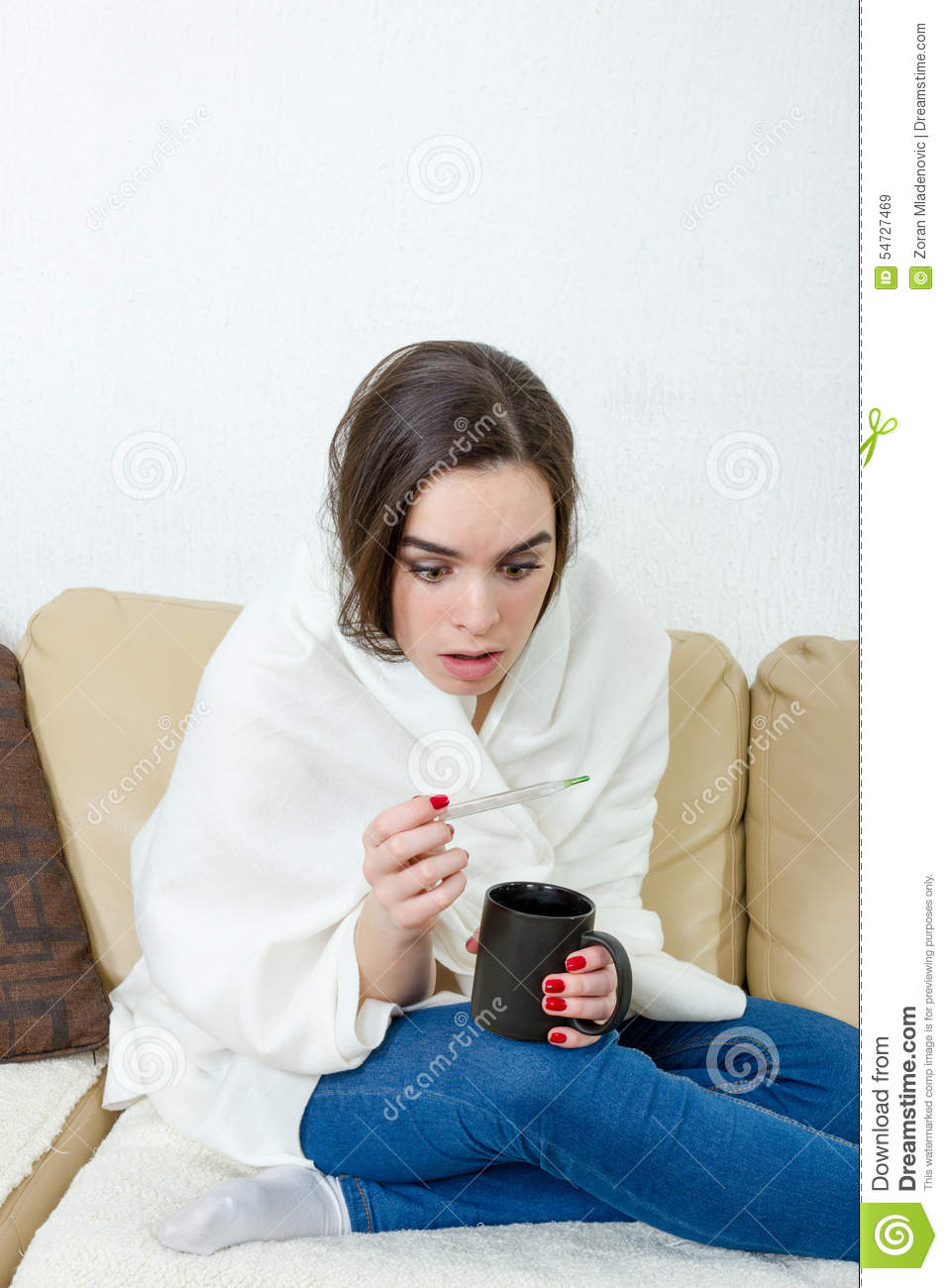 Female model caught cold covered with white blanket at home.