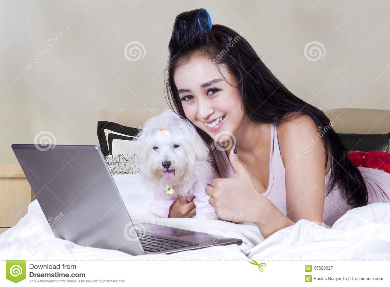 Female model with dog and notebook on bed