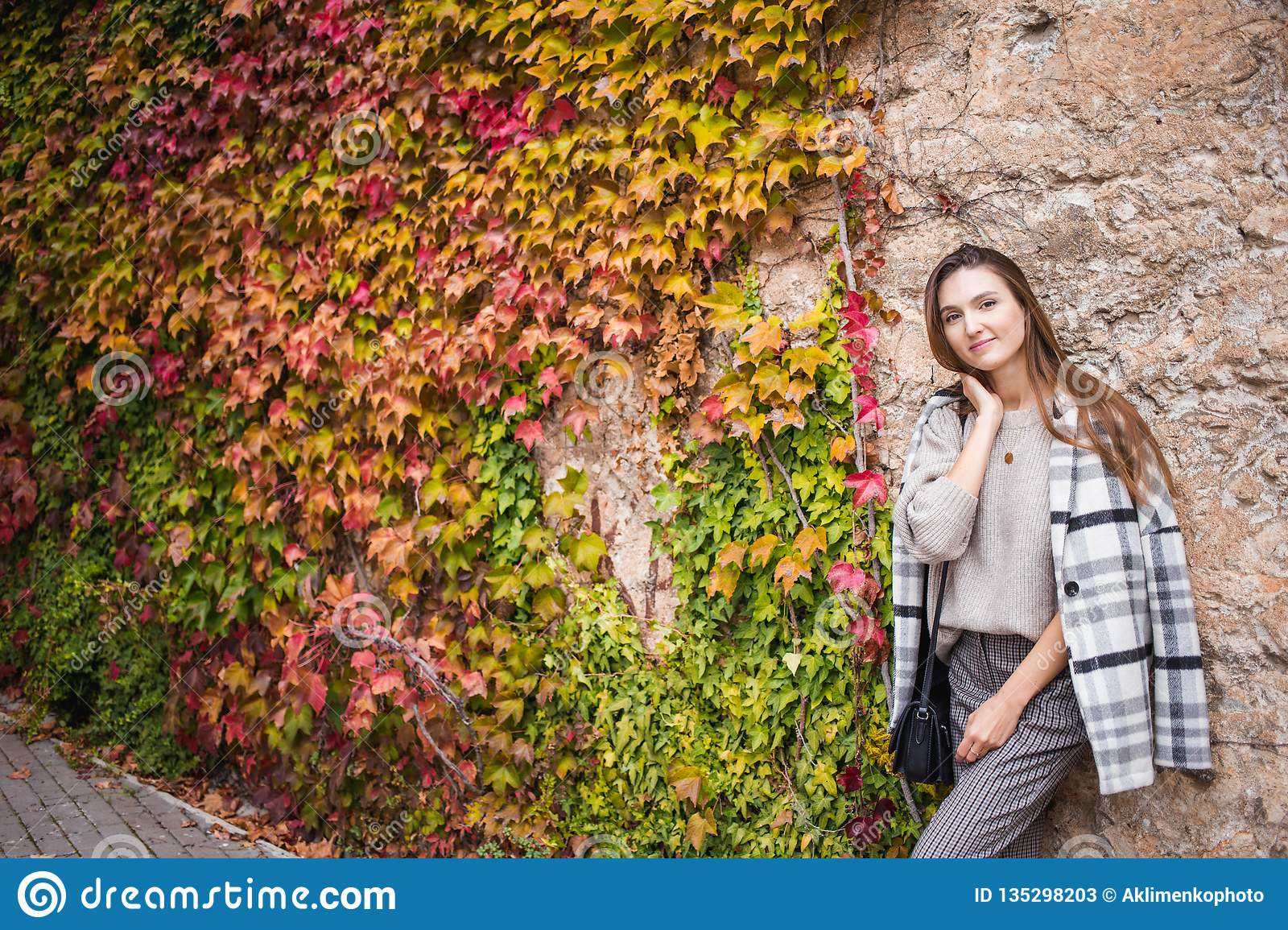 Female model in trendy outfit on the steet wall background