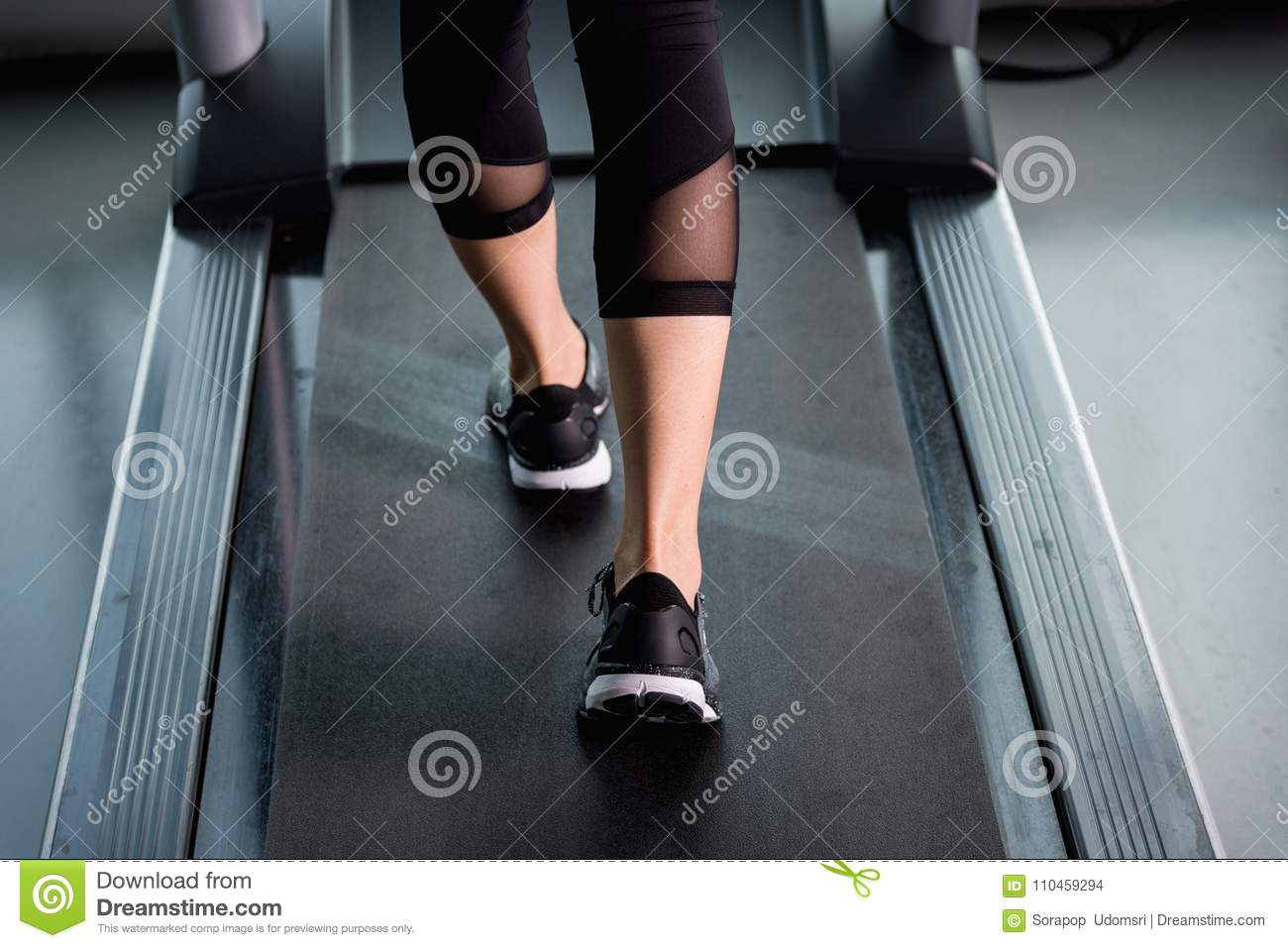 Female Muscular Feet In Sneakers Running On Treadmill At Gym Stock