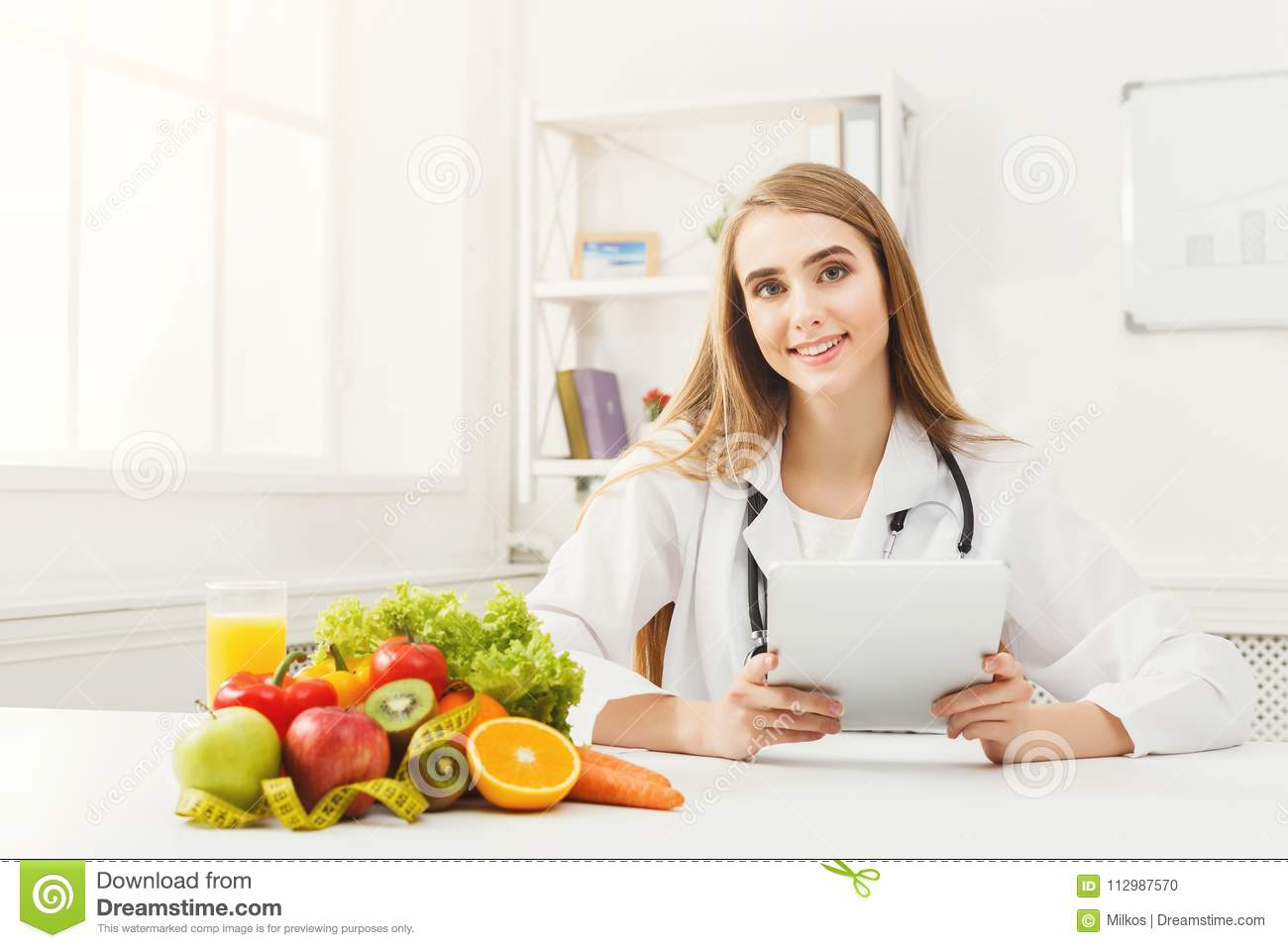 Female nutritionist working on digital tablet