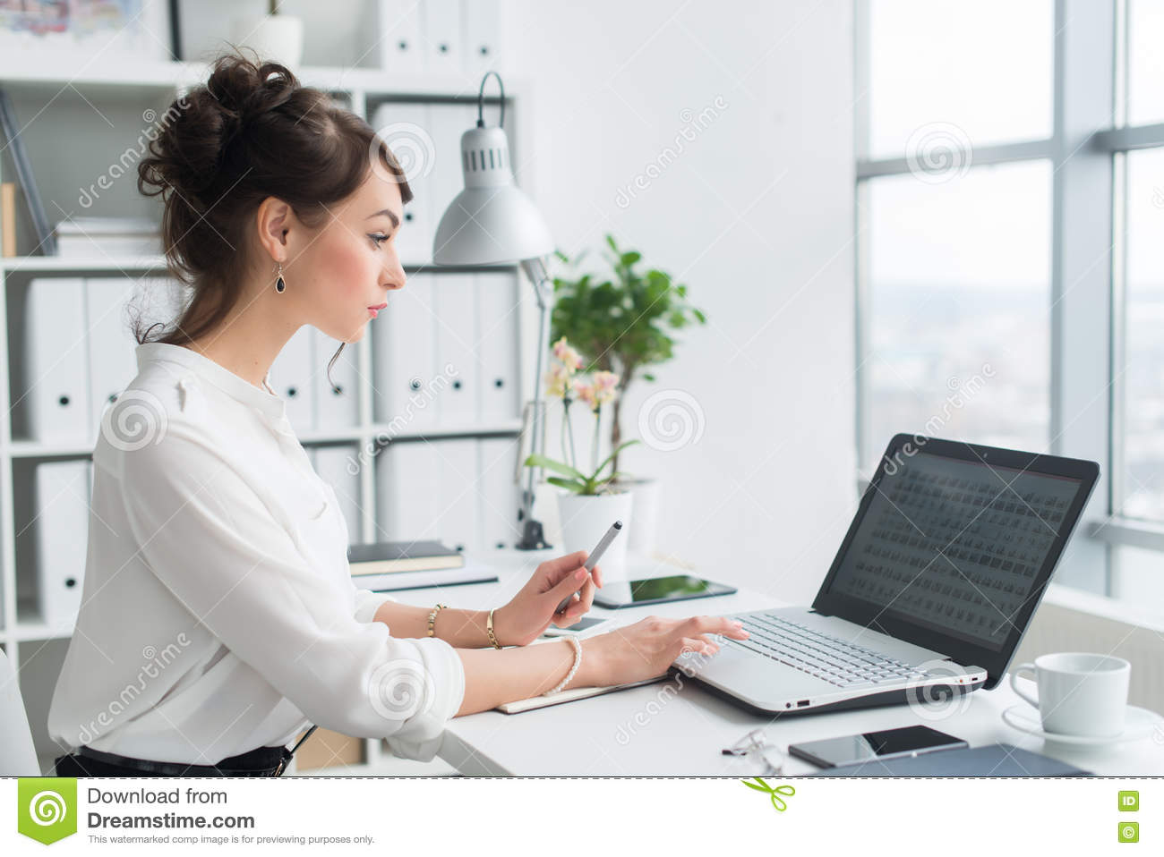 Female office worker using laptop at her workplace, browsing information, surfing the internet, side view portrait.