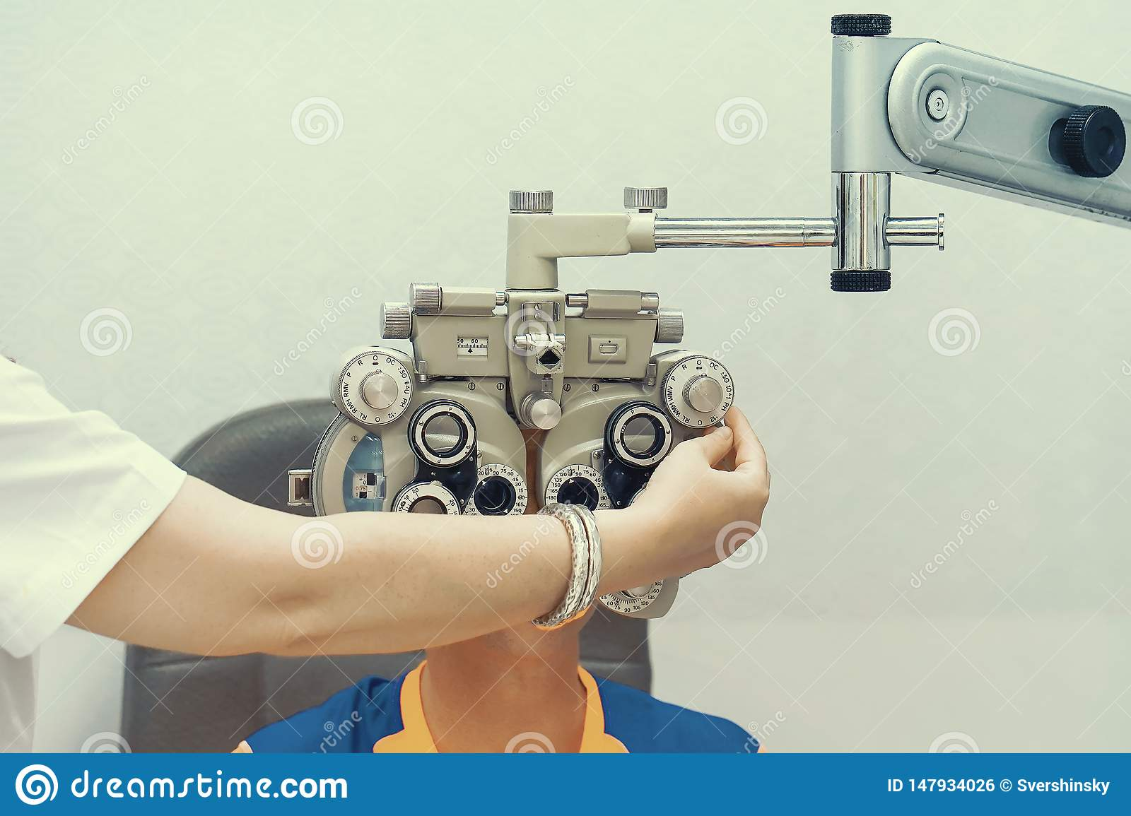 Female Optometrist Doing Sight Testing For Male Patient In Clinic