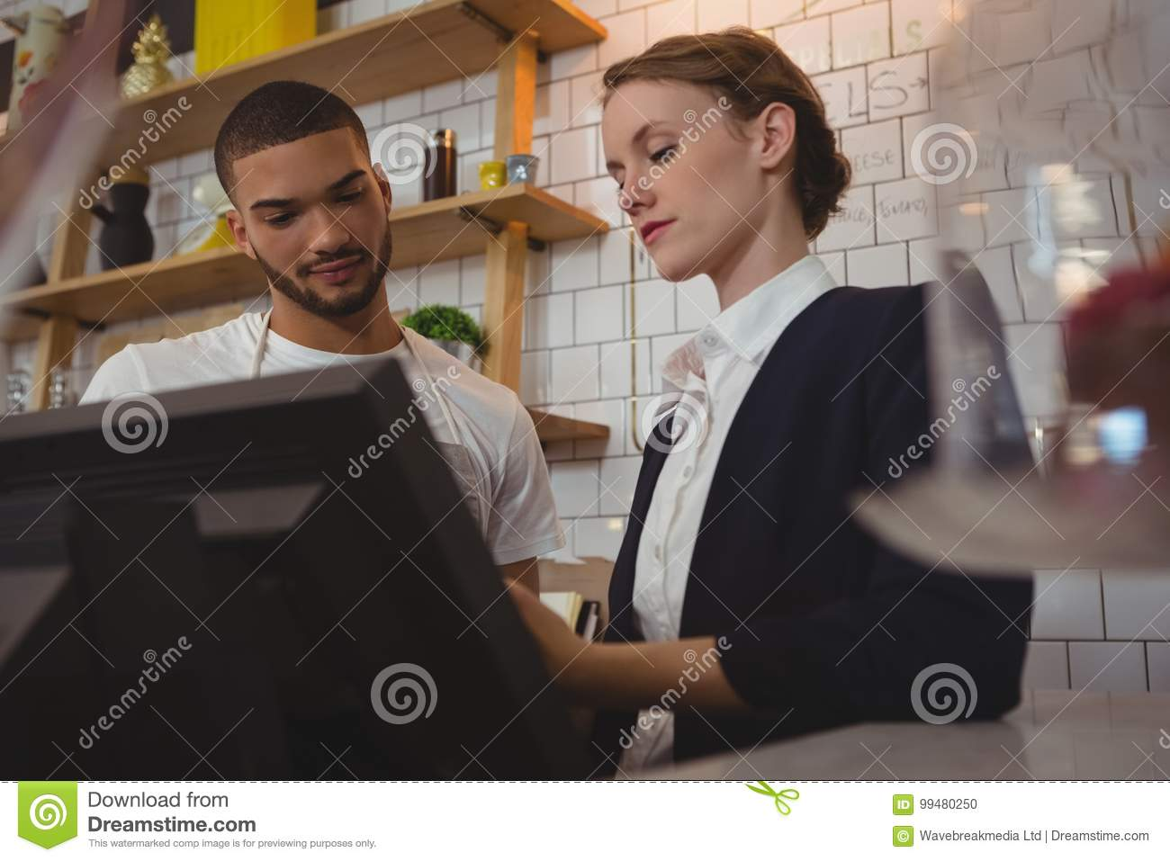 Female owner with waiter using cash register in cafe