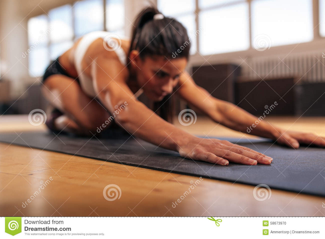 Female Performing Yoga On Exercise Mat At Gym Stock Photo